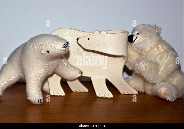 Ceramic and stuffed toy polar bears on teakwood table - Stock-Bilder