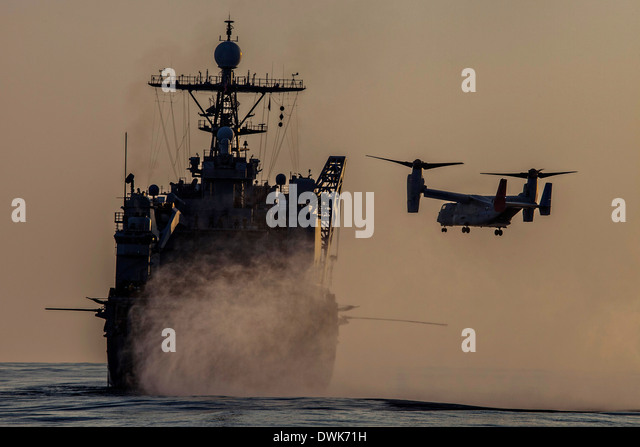 A US Marine Corps MV-22 Osprey comes in to land on the Whidbey Island-class dock landing ship USS Ashland February - Stock Image