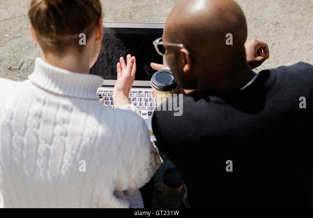 High angle view of business people working on laptop outdoors - Stock-Bilder