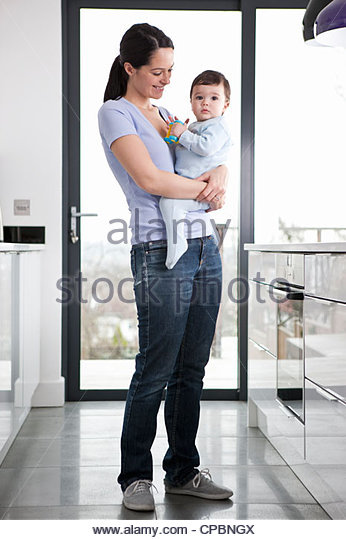 A mother standing in a kitchen holding her baby son - Stock-Bilder
