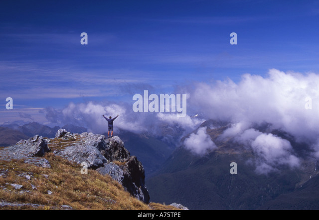 Man Triumphant having reached the summit of Conical Hill on The Routeburn Track South Island New Zealand - Stock Image