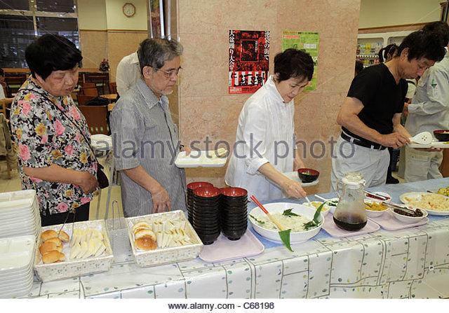 Tokyo Japan Ikebukuro Toyoko-Inn Ikebukuro Kita-guchi No.2 hotel breakfast room buffet table Asian woman women man - Stock Image