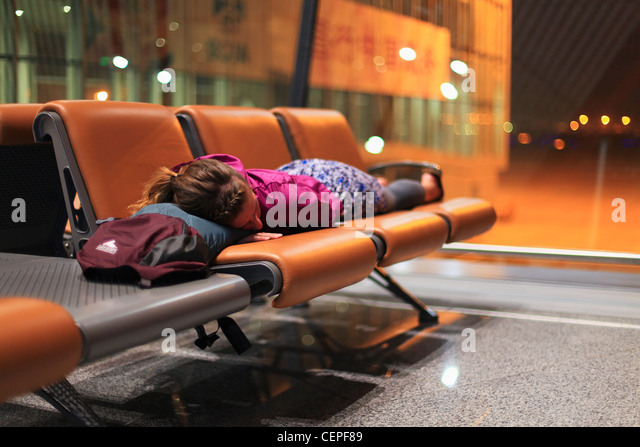 a girl sleeping on chairs at an airport; beijing, china - Stock-Bilder