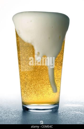 beer glass overflowing - Stock Image