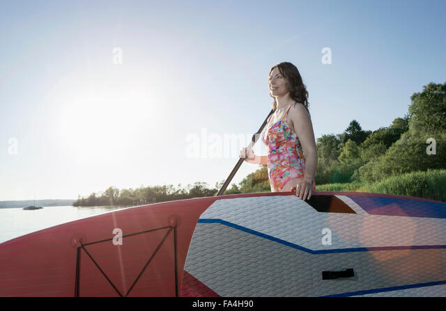 Mature woman carrying stand up paddle board at lakeshore, Bavaria, Germany - Stock Image