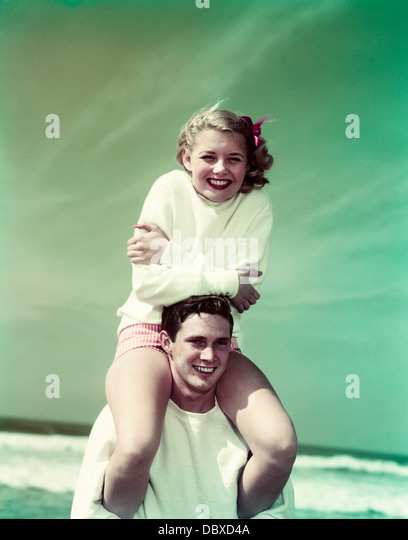 1940s 1950s SMILING TEEN COUPLE AT BEACH GIRL SITTING ON BOYS SHOULDERS LOOKING AT CAMERA - Stock Image