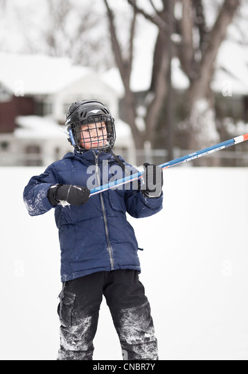 Boy playing ice hockey, outdoor rink, Winnipeg, Manitoba, Canada - Stock Image