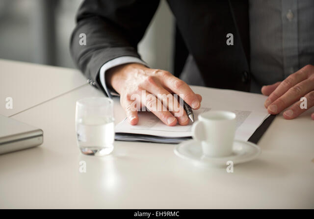Businessman reviewing document, cropped - Stock Image