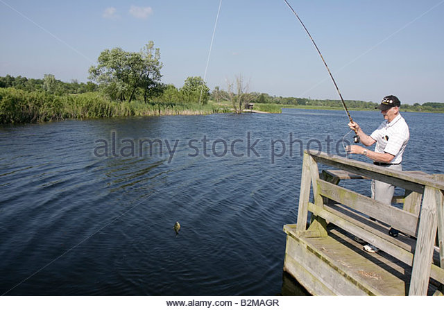 Wisconsin Kenosha Kansasville Richard Bong State Recreation Area Wolf Lake Fishing Pier man senior angler water - Stock Image