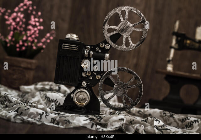 Small nostalgic decorative film camera on brown wooden background - Stock Image