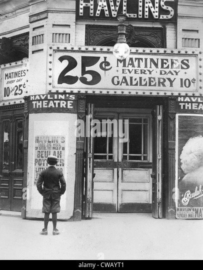 Boy in front of a movie theater showing a film with Beulah Poynter, original caption quote: 'Where the boys - Stock Image