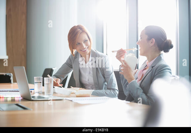 Smiling young businesswomen having lunch at table in office - Stock Image