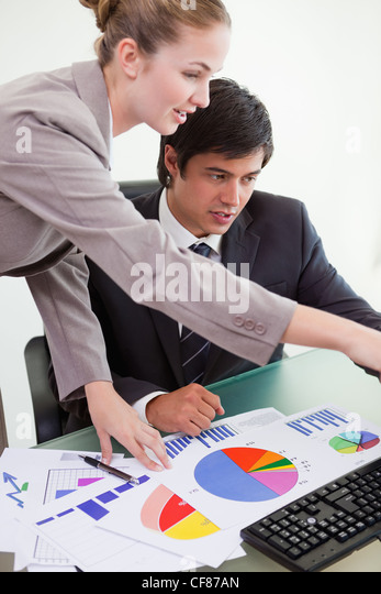 Portrait of a professional business team studying statistics - Stock Image
