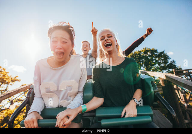 Enthusiastic young friends riding roller coaster ride at amusement park. Young people having fun at amusement park. - Stock Image