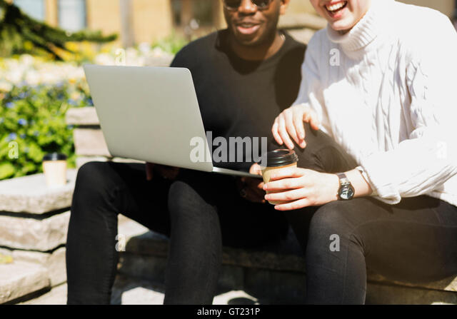Midsection of woman holding coffee cup while man with laptop on steps - Stock-Bilder
