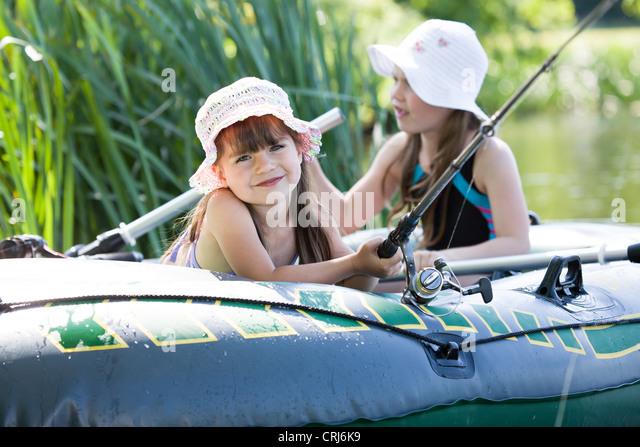 little girls fishing on lake at summer - Stock Image