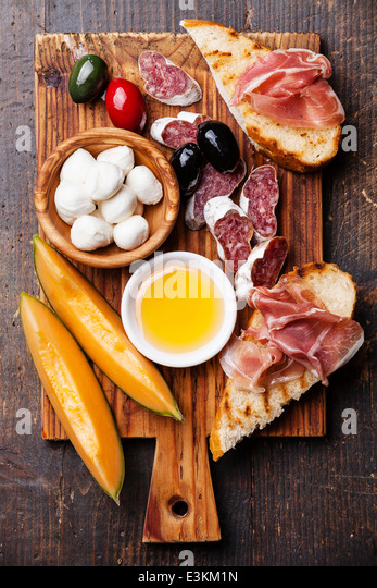 Prosciutto ham, Slices of melon cantaloupe, Mozzarella cheese and Olives on cutting board - Stock Image