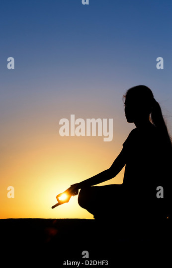 Sunset silhouette of an Indian girl meditating. Andhra Pradesh, India - Stock-Bilder