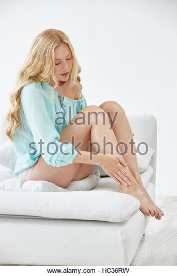 Portrait of young woman sitting on sofa touching leg. - Stock Image