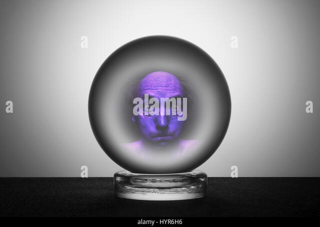 Crystal ball with tense frightened face - Stock Image