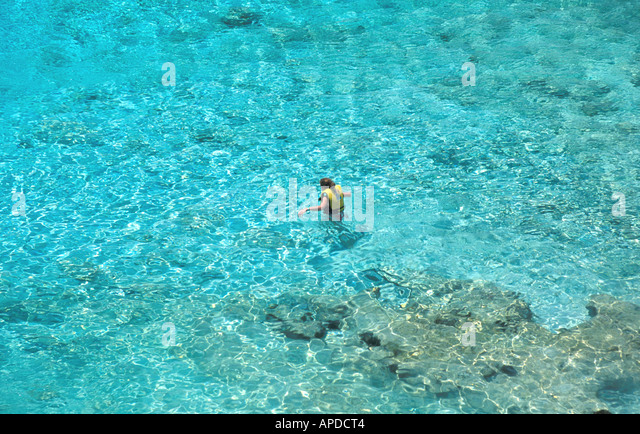 Tropics tropical woman in life jacket standing in crystal clear water - Stock Image
