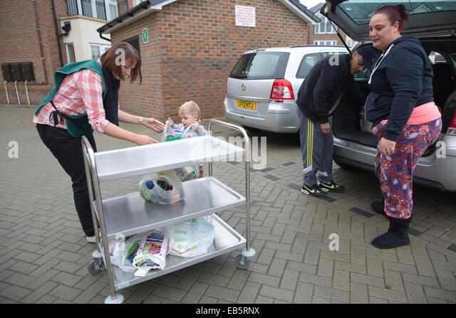 A family receiving food at Epsom Foodbank, food donations for families suffering from financial difficulty, Surrey, - Stock Image