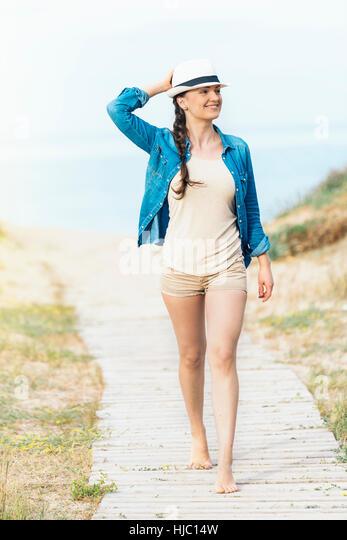 Pretty woman walking away on the idylic beach. - Stock Image