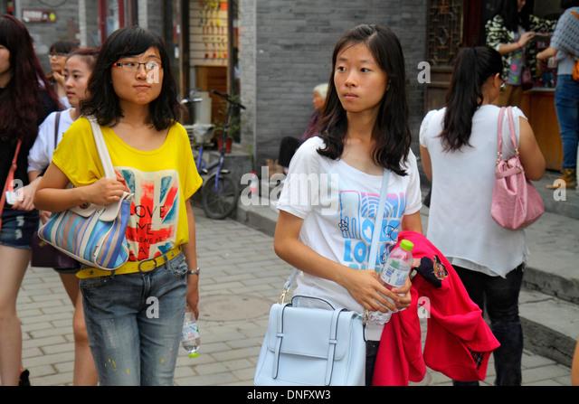 China Beijing Dongcheng District Nanluoguxiang hutong historic shopping Asian woman friends walking - Stock Image