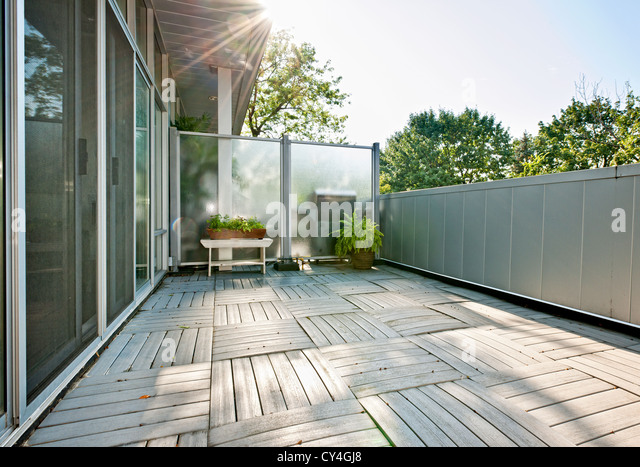Spacious balcony of modern condo with plants on sunny day - Stock Image
