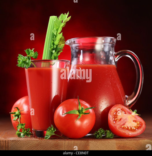 Still life: tomatoes, jug and glass full of fresh tomatoes juice on wooden table. - Stock Image