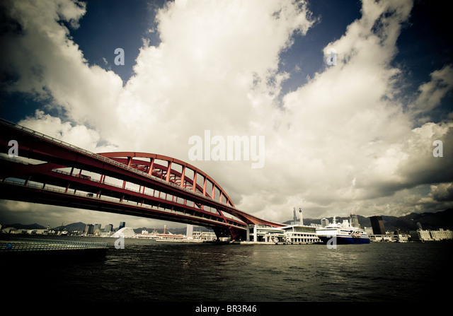 A cruise ship docked in the Kobe harbor with the bridge to Port Island visible in the foreground, Kobe, Japan (toned - Stock Image