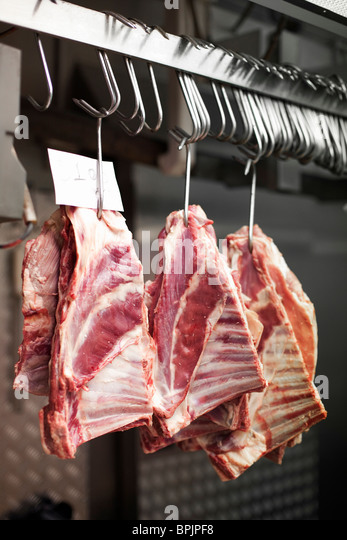 3 Chunks of beef ribs on meat hooks hanging in stainless steel kitchen or freezer - Stock Image