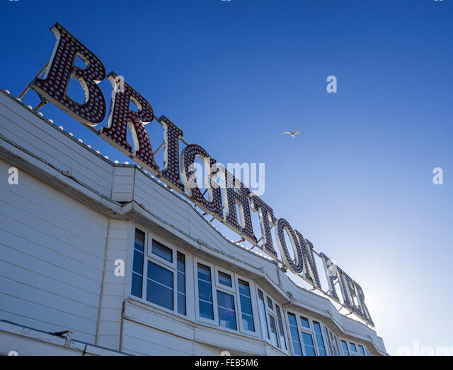 Brighton Pier sign and seagull in a clear blue sky - Stock Image