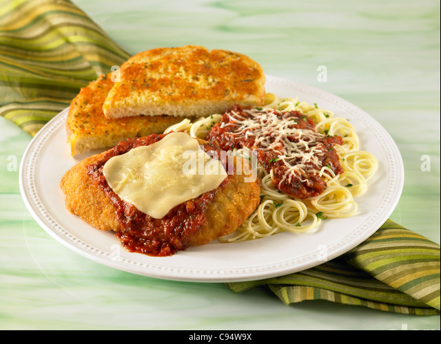 Chicken Parmesan dinner with pasta served with garlic bread - Stock Image