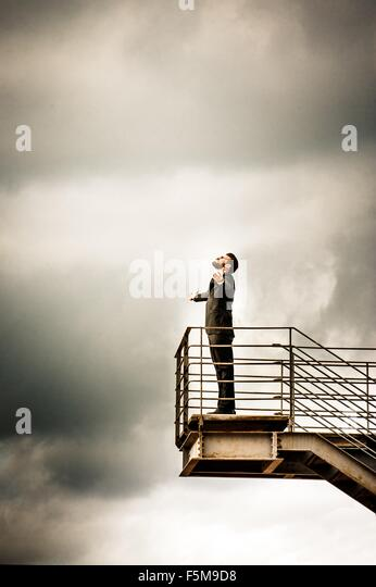 Low angle side view of mid adult man on stairs wearing suit, arms open throwing head back - Stock Image