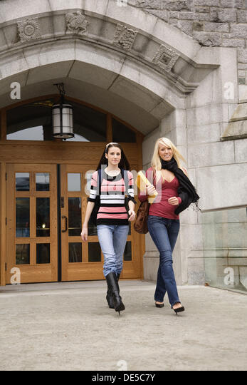 Two female college students walking out of a building, University of British Columbia, Vancouver, BC, Canada - Stock Image