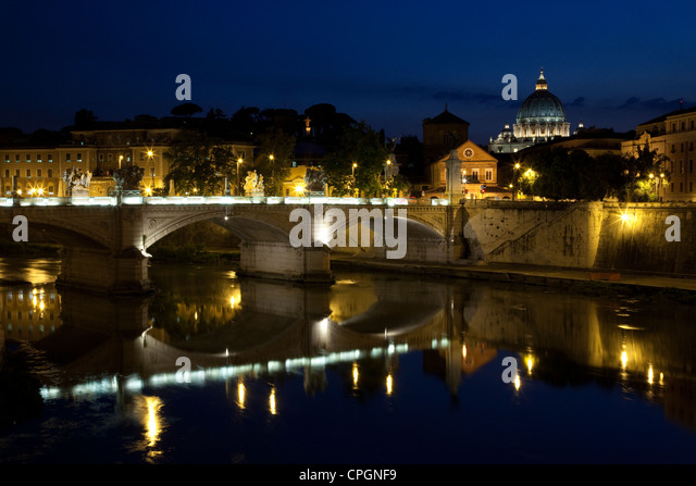 St. Peter's Basilica and the lights from the Ponte Vittorio Emanuele II are reflected in the Tiber river, Rome, - Stock Image