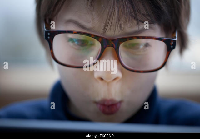 Close up of boy pulling a face using digital tablet - Stock Image