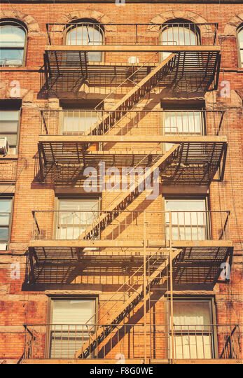 Retro style photo of New York building with fire escape ladders, USA. - Stock-Bilder