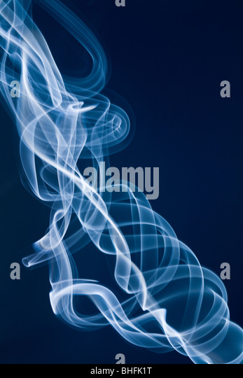 Jet of white smoke against a blue background - Stock Image