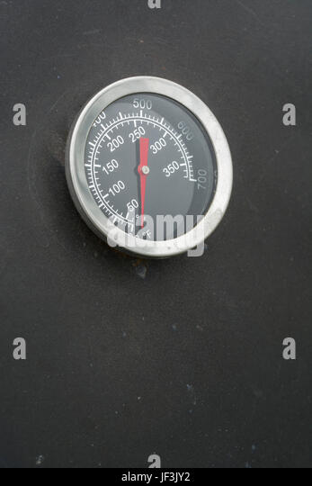 Temperature gauge on the exterior of a barbecue / bbq smoker not fired up. Possible visual metaphor for concept - Stock Image