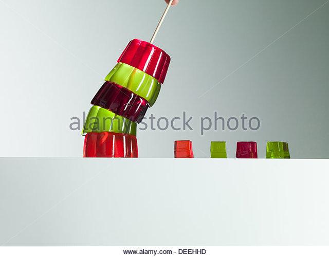 Stack of vibrant gelatin dessert leaning over small gelatin dessert cubes - Stock Image