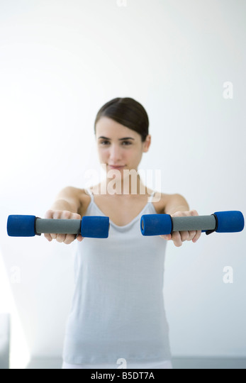 Young woman holding out pair of dumbbells, smiling at camera - Stock Image