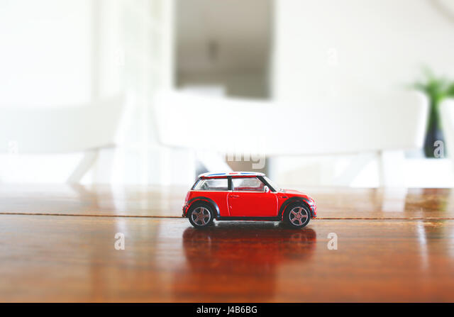 Red toy car in red color on a wooden table in a bright indoor environment - Stock Image