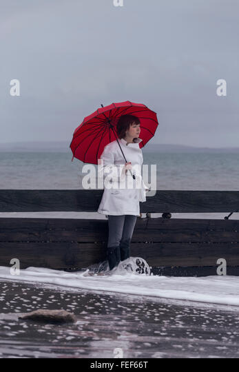 a woman in a white coat with a red umbrella at the sea in winter - Stock Image