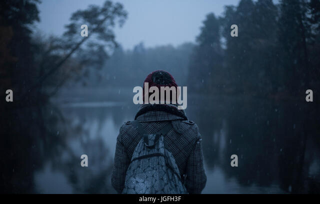 Woman carrying backpack standing near still lake - Stock Image