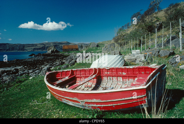 Beached red rowing-boat and solitary white cloud in a blue sky, at Ord, Sleat, southern Skye, western Scotland, - Stock Image