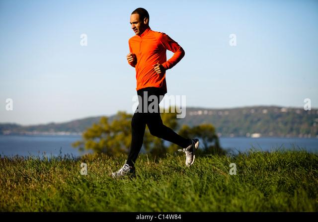 A man wearing an orange shirt runs along a trail in Rockefeller State Park in Sleepy Hollow, New York. - Stock Image