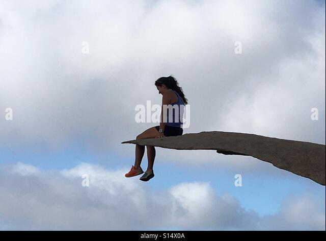 Sitting on the edge of a rock in the clouds - Stock-Bilder