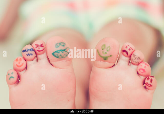 Girls feet with smiley face drawings - Stock-Bilder